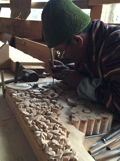 Man curving wood, traditional way of woodcurving in Bhutan