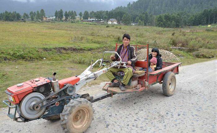 A farmer giving ride to his family on his power tiller