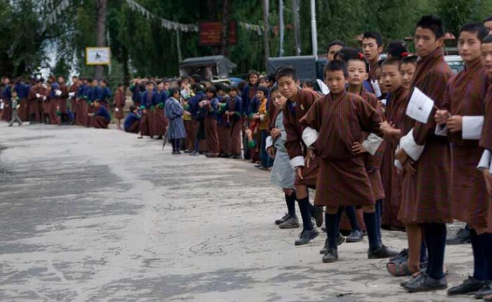 School children lined up by the roadside cheering participants of the world's toughest one-day mountain bike race